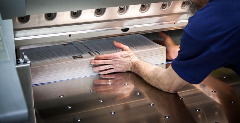 imprimerie façonnage massicot main qui taque le papier dans le massicot